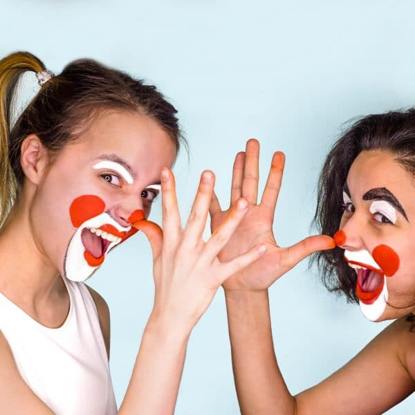 Two teenage brunettes in t-shirts and with painted faces jokingly show their long noses with their fingers palm. Isolated on gray. Family celebrates April Fool's Day.